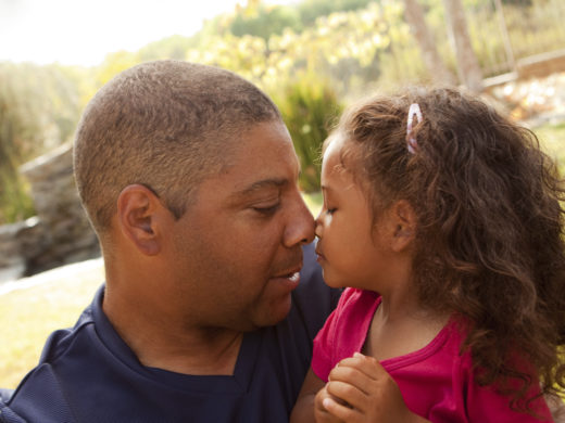 Father and young daughter eskimo kiss