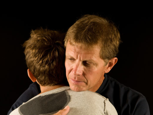 Father emotionally hugs preteen son - consoling, comforting, or making up after argument